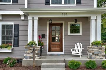 Welcoming front entrance to house has a chair and plants on porch