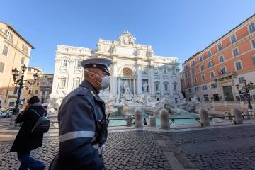 An Italian police officer patrols the Trevi Fountain in Rome