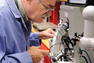 Russell Taylor, the John C. Malone Professor, tests a robot designed to help surgeons keep a steady hand