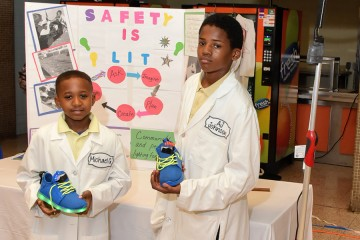 Two students hold up their LED sneaker prototypes