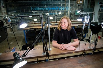 A woman sits at a work bench with her arms folded. There are adjustable lamps on all the workspaces, as well as various tools
