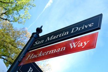Hackerman Way on red street sign under dark blue San Martin Drive sign
