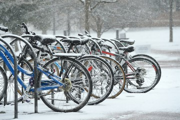 Bikes lines up in a bike rack in the snow