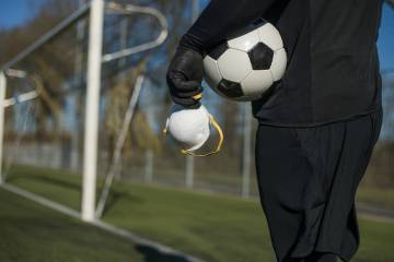 A man holds a soccer ball and a mask on a soccer field