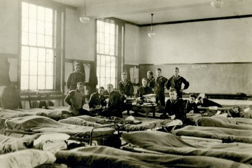 Black and white photo shows young soldiers in training lounging in their barracks
