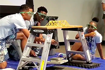 Student team hangs weights from a spaghetti bridge