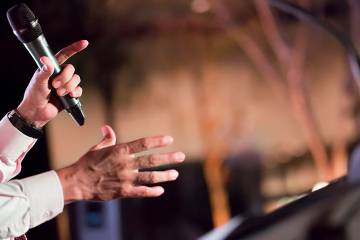Man's hands holding a microphone