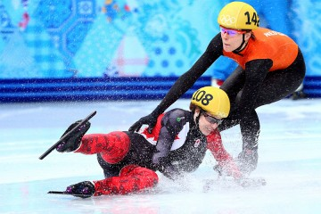 A short track speed skater falls in front of another skater