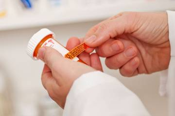 Pharmacist applying a drug-warning label to a pill container