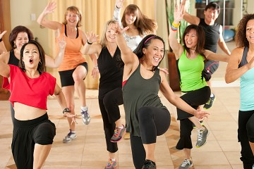 A group of women and men do dance moves in an exercise class