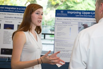 Lydia Carroll speaks with a poster session attendee