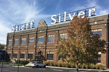 Exterior of the Stieff Silver building depicts a brick building topped with a giant Stieff Silver sign