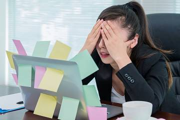 Stressed woman sitting at laptop covered with sticky notes