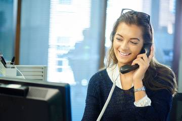 Young woman at computer talking on phone