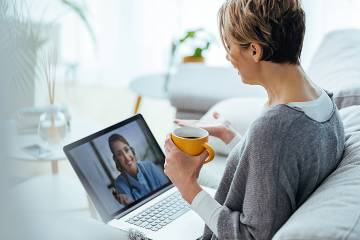 A woman sitting in bed with her laptop confers with a doctor on the screen