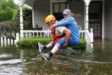 Man in yellow helmet, orange vest carries woman piggyback style amid waist-deep floodwaters in Houston