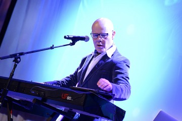 Thomas Dolby at keyboard with blue background