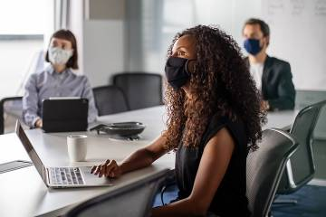 People wearing masks meeting in an office