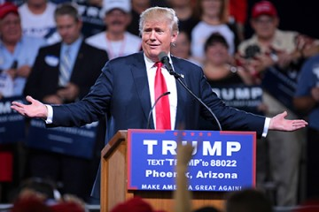 Donald Trump shrugs at podium at Phoenix rally