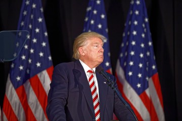 Donald Trump in front of three American flags