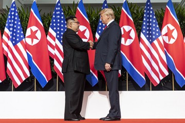 Trump and Kim shake hands in front of backdrop of U.S. and North Korean flags