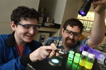 Tyrel McQueen (right) and a student observe how experimental materials respond to light