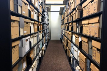 A row between two shelving units filled with boxes