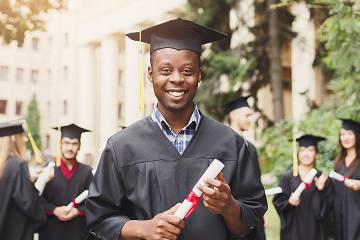 Young man in cap and gown holding a diploma on graduation day