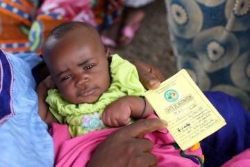 Baby held by parent who also holds a vaccination card