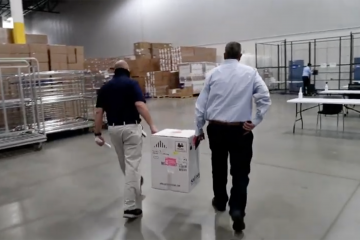 Two men carry a box between them