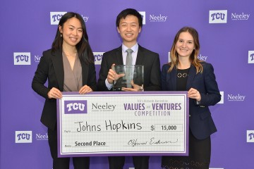 Three students pose with an oversized check for $15,000