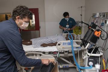 Two scientists test a robot in an ICU simulation room