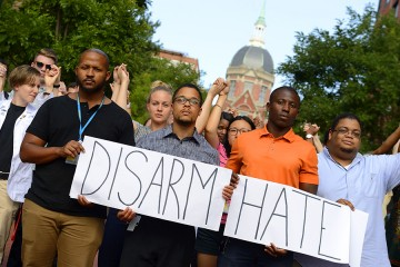 Vigil attendees hold a sign that reads 'Disarm Hate;' the Johns Hopkins Medicine dome can be seen in the background
