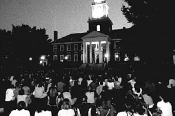 Black and white photo of a group of people sitting on the quad