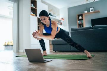 Woman exercising in front of a laptop placed on the floor