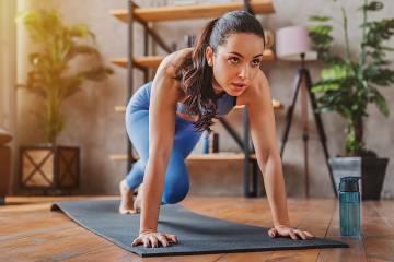 Woman in yoga position facing a TV screen