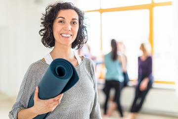 Smiling woman carrying a yoga mat in an exercise room