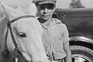 A black and white photo shows a boy in a newsy cap holding the reins of a white horse