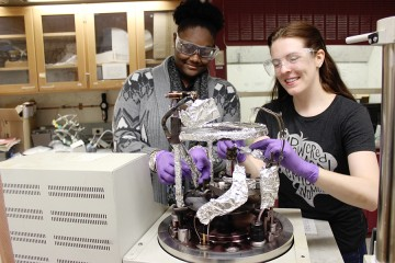 Two women wearing safety goggles attach foil to a piece of lab equipment