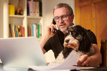 Man working at computer on table at home with dog on his lap