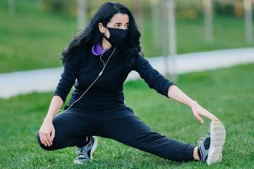 Young woman wearing mask and stretching on grass
