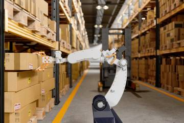 A robot in a wharehouse reaching for boxes