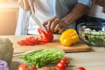 Closeup of man's hands preparing salad