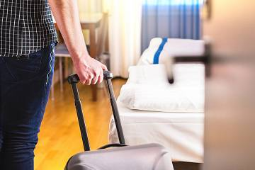 Man pulling suitcase entering a hotel room