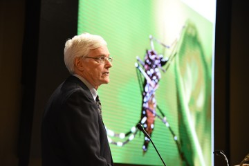 Thomas Quinn stands in front of a slide depicting the mosquito responsible for the transmission of Zika