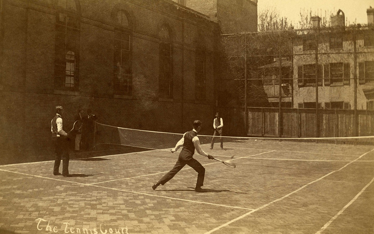 Men in suit vests play tennis