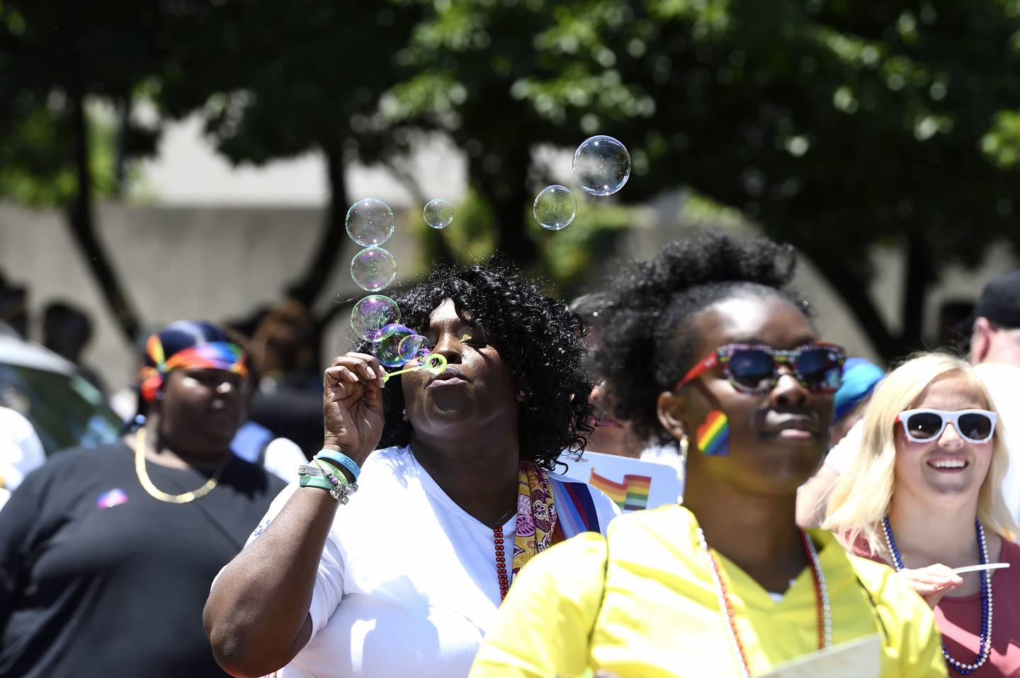 A woman blows bubbles at Pride