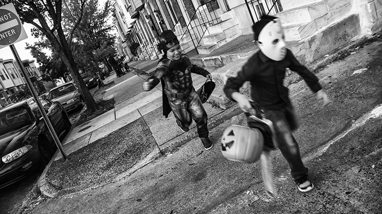 Two boys run in Halloween costumes