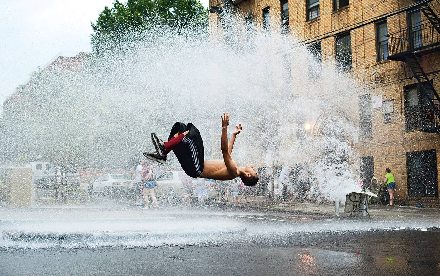 A man does a backflip in the spray of an open fire hydrant