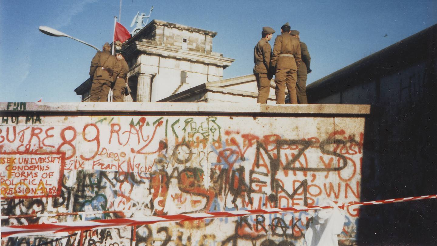 Soldiers stand atop the Berlin Wall in November 1989